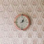 retro oink clock on a vintage style wallpapered wall